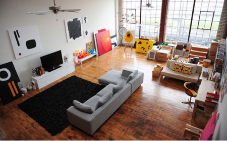 Contemporary-living-room-with-gray-sofa-black-carpet-wood-floor-and-hight-windows-and-picture-of-walls